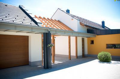 Családi ház homlokzata - Nyeregtető pergolával, garázskapuval - homlokzat ötlet, modern stílusban