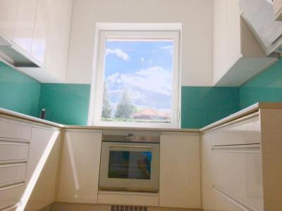 Magasfényű fehér konyhabútor, színre fújt élfogantyúkkal, türkiz zöld, edzett üveg hátfallal - konyha / étkező ötlet, modern stílusban